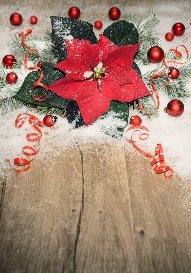 Fondo di Natale con la stella di Natale, le bagattelle rosse e la neve sul wo fotografia stock libera da diritti
