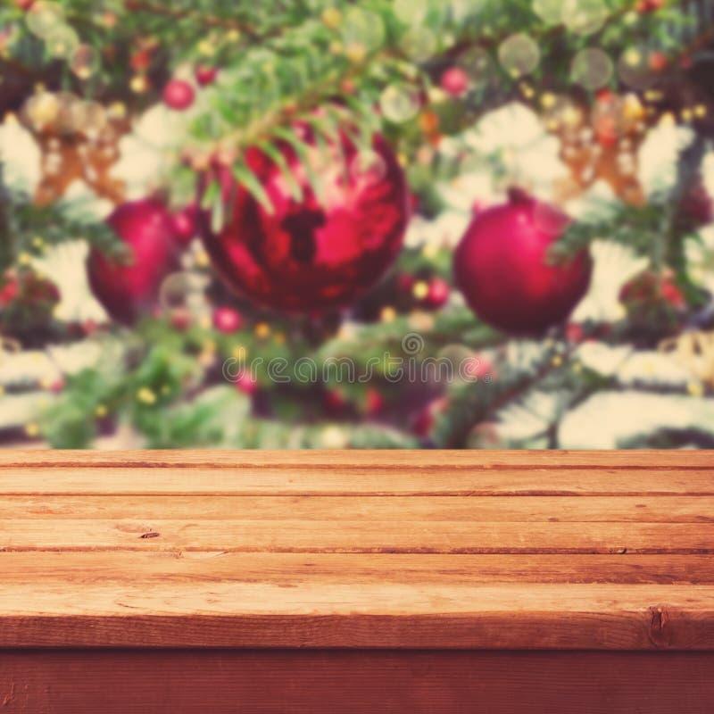 Fondo di Natale con la tavola di legno vuota della piattaforma sopra le decorazioni dell'albero di Natale fotografia stock