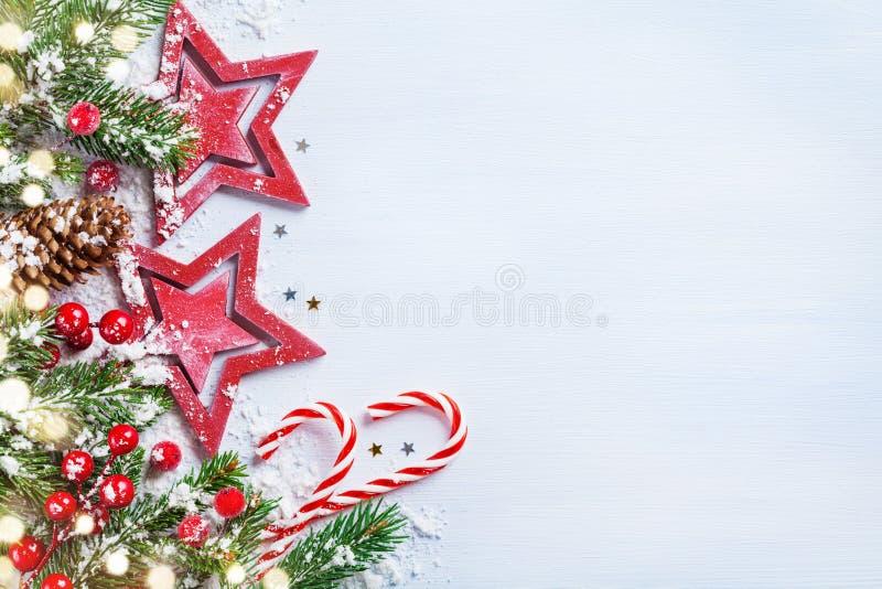 Fondo di Natale con le stelle, i rami nevosi dell'abete, i coni e le luci del bokeh Insegna o carta di festa immagine stock