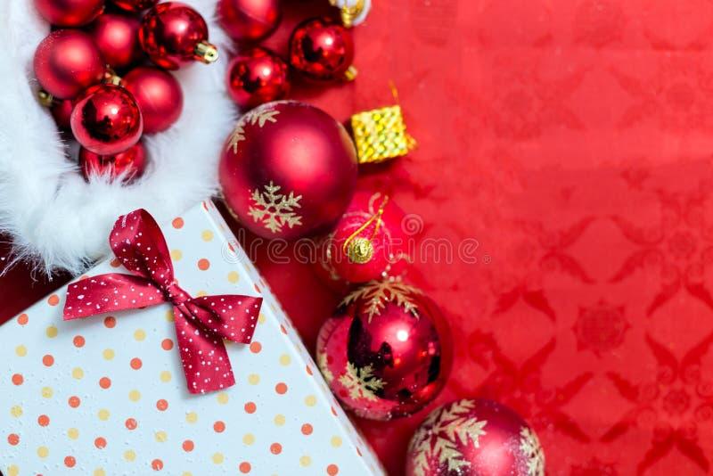 Fondo di Natale con un ornamento rosso, un contenitore di regalo dorato e un fi illustrazione vettoriale