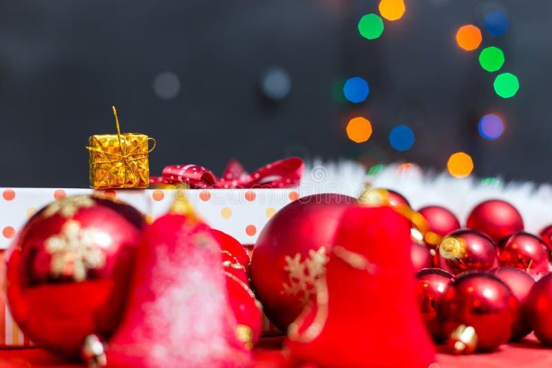 Fondo di Natale con un ornamento rosso, un contenitore di regalo dorato e un fi illustrazione di stock
