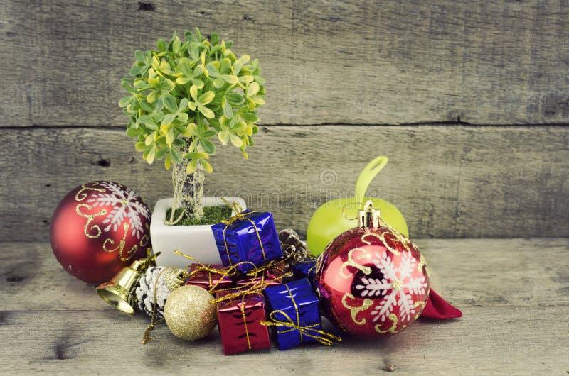Fondo di Natale con un ornamento rosso, un contenitore di regalo rosso e blu e un albero verde artificiale fotografia stock