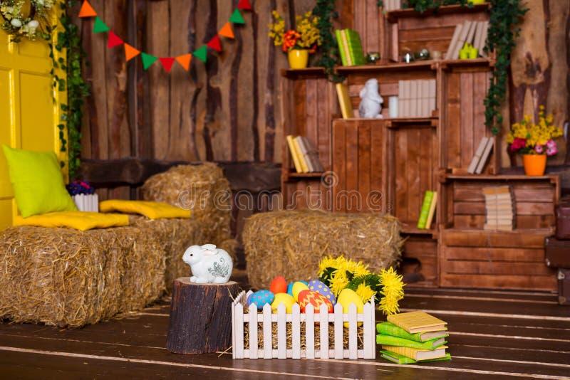 Fondo di Pasqua con le uova variopinte, il coniglietto bianco ed i fiori gialli sopra vecchio legno immagine stock