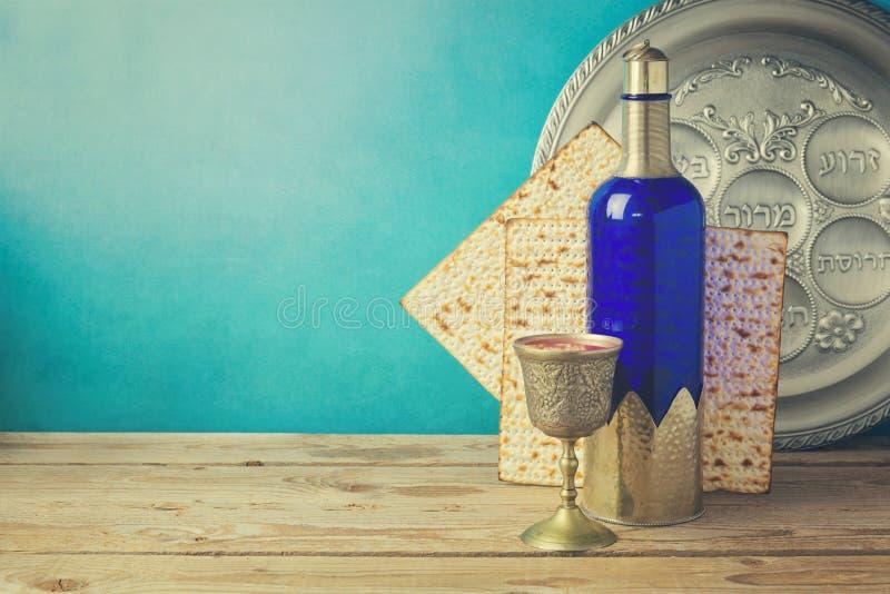 Fondo di pesach con il pane azzimo ed il vino sulla tavola d'annata di legno Piatto di Seder con testo ebraico immagini stock