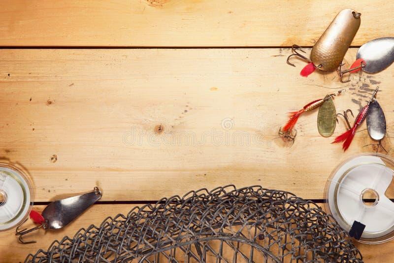 Fondo di pesca con varia attrezzatura di pesca con l'amo sulle plance di legno fotografie stock