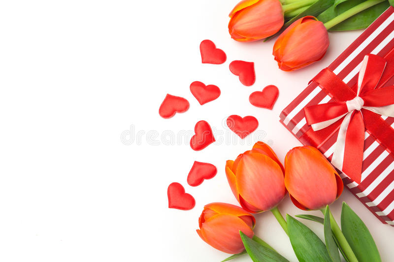 Fondo di San Valentino con i fiori del tulipano ed il contenitore di regalo su bianco fotografia stock libera da diritti