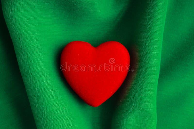 Fondo di San Valentino. Il cuore rosso su verde piega il panno immagine stock libera da diritti