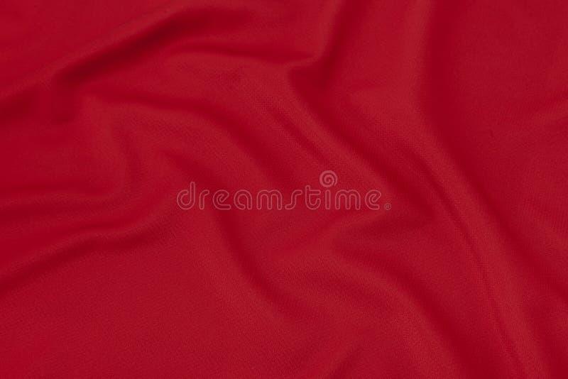 Fondo di struttura del tessuto dell'abbigliamento di sport La camicia rossa di calcio, può usare per progettazione fotografie stock libere da diritti