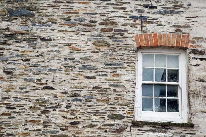 Fondo di struttura della parete di pietra con la finestra di telaio fotografia stock