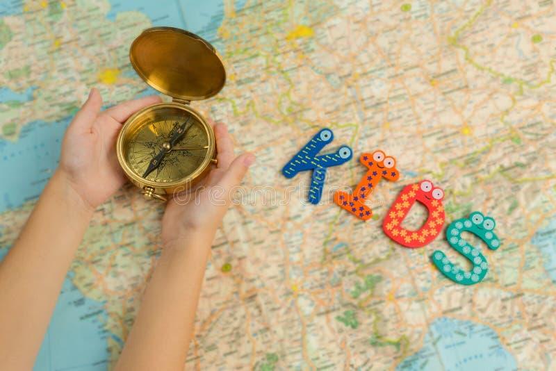 Fondo di tema di viaggio del ` s del bambino Il bambino passa la bussola dell'oro della tenuta sotto la mappa fotografia stock libera da diritti