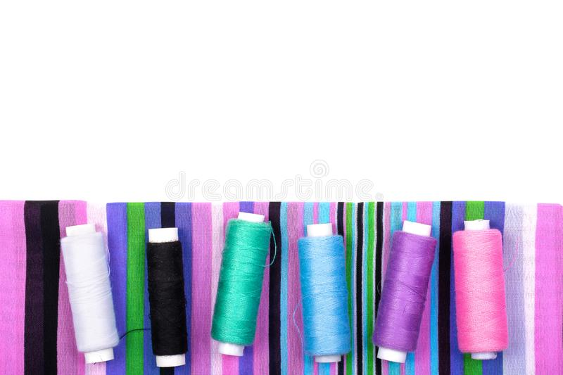 Fondo di tessuto a strisce e bobine dei fili dei colori differenti su un fondo bianco fotografia stock