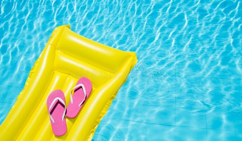 Fondo di vacanza estiva della spiaggia Materasso di aria gonfiabile, Flip-flop sulla piscina Accessori gialli di estate e di lilo immagini stock libere da diritti