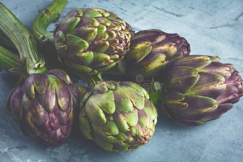 Fondo di verdure con il fondo grigio dei carciofi freschi fotografia stock