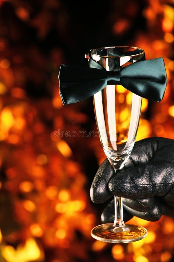 Fondo di vetro dell'oro della cravatta a farfalla del champagne nero dei guanti di cuoio fotografia stock libera da diritti