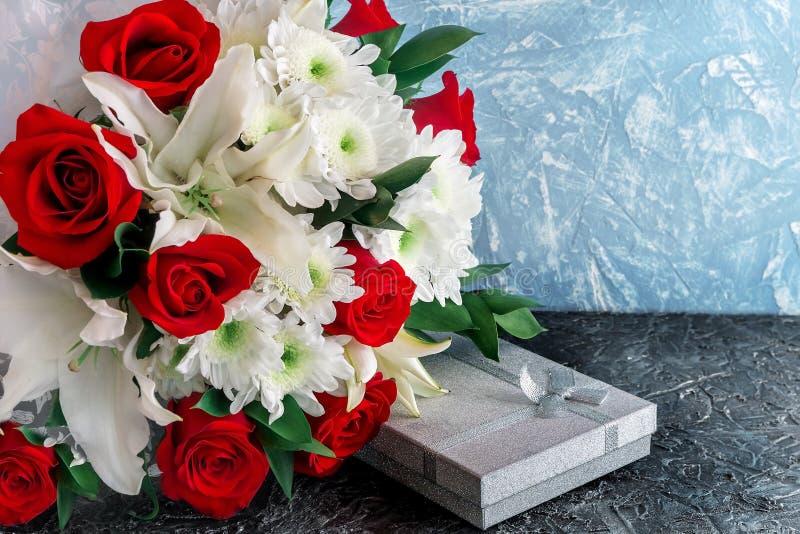 Fondo, disposizione per le congratulazioni alle donne Un mazzo dei fiori dalle rose, dai gigli e dai crisantemi con un regalo in  fotografia stock libera da diritti
