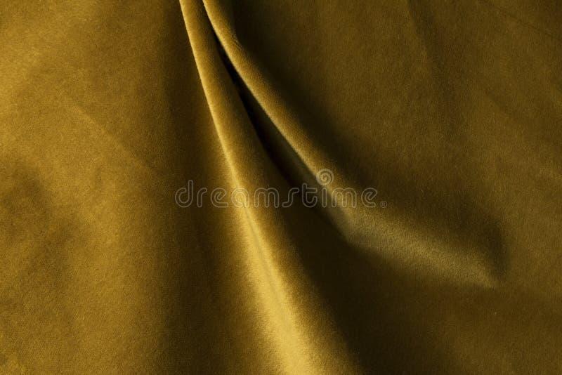 Fondo dorato del tessuto del velluto, velluto, mohair, effetto del cashmere fotografia stock
