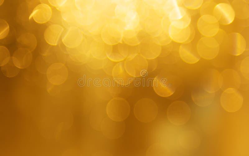 Fondo dorato della luce di festa, belle scintille brillanti fotografia stock libera da diritti