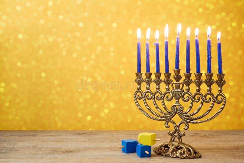 Fondo ebreo di Chanukah di festa con il dreidel d'annata della trottola e del menorah sopra il bokeh delle luci fotografie stock