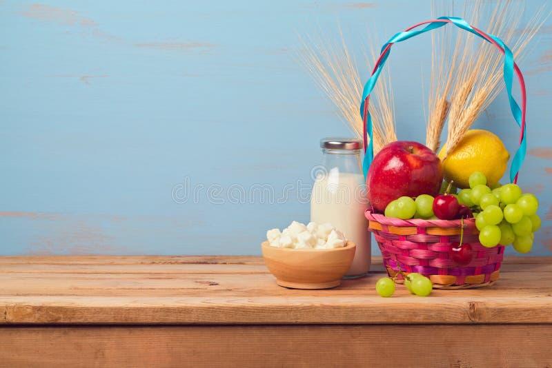 Fondo ebreo di Shavuot di festa con il canestro di frutta e della bottiglia per il latte fotografia stock