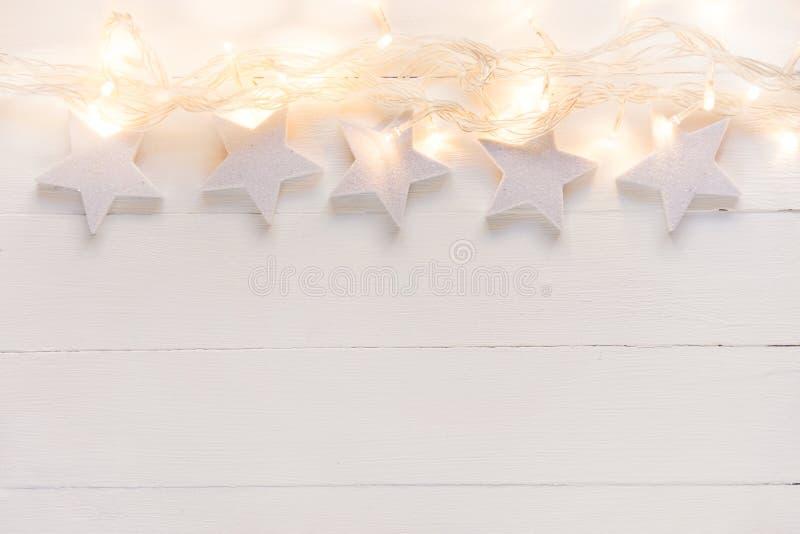 Fondo elegante hermoso del Año Nuevo de la Navidad Guirnalda de oro chispeante de las luces de las estrellas blancas en la madera foto de archivo libre de regalías