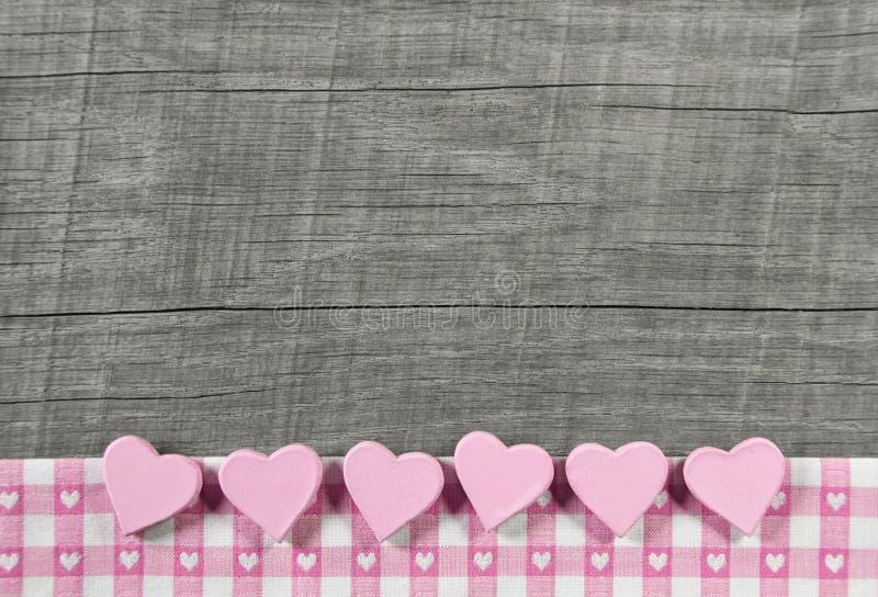 Fondo elegante misero grigio di legno con i cuori rosa su una r bianca fotografie stock