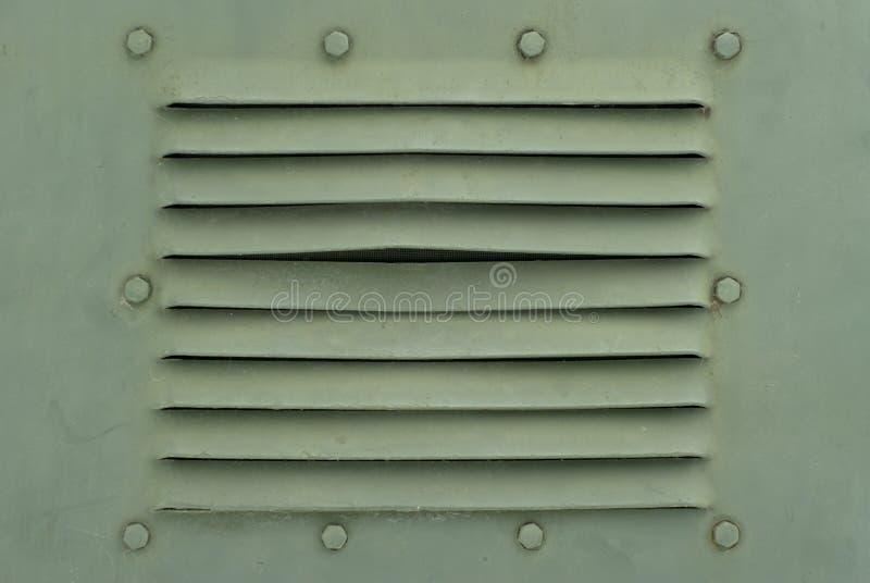 Fondo en el estilo militar: una sección de una pared del metal o de una cáscara del vehículo blindado con los pernos y las rajas  fotos de archivo