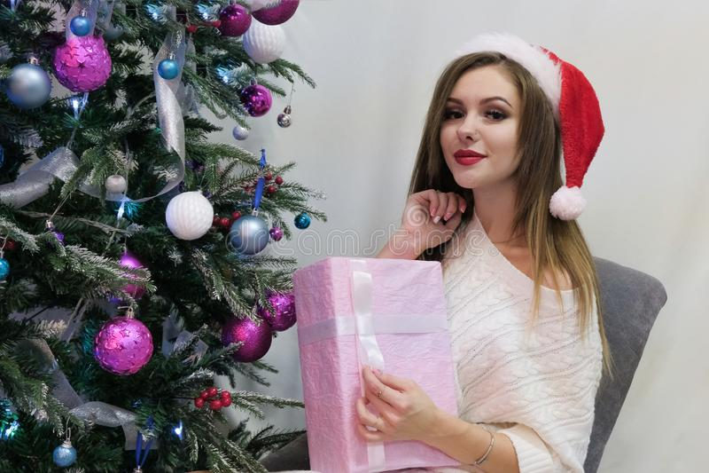 Fondo en el tema de una Feliz Año Nuevo La muchacha atractiva hermosa en un sombrero rojo, suéter hecho punto se sienta al lado d imagen de archivo