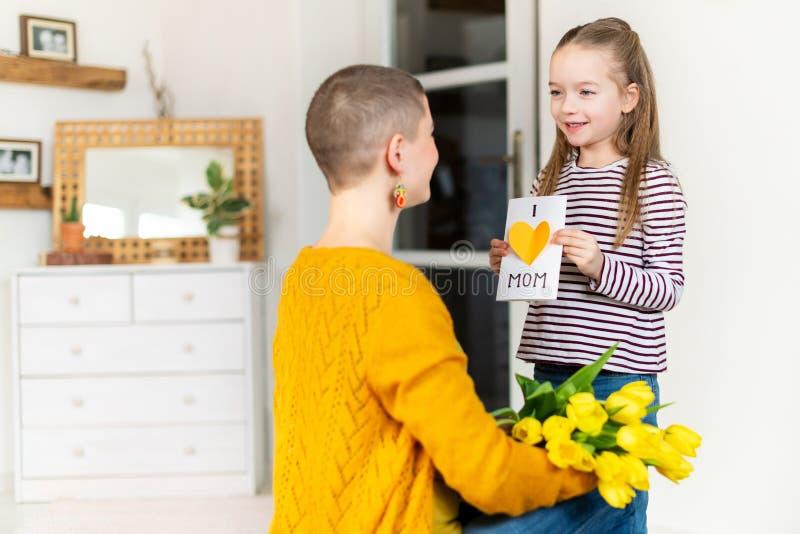 Fondo felice di compleanno o di festa della Mamma Ragazza adorabile sorprendente la sua mamma con la cartolina d'auguri casalinga fotografie stock libere da diritti
