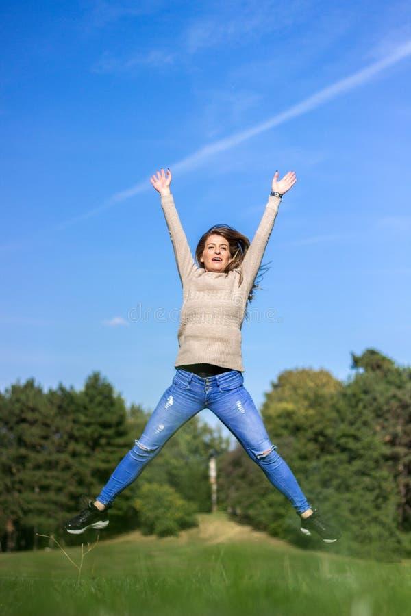 Fondo feliz del salto joven, del cielo y del árbol de la mujer imagen de archivo