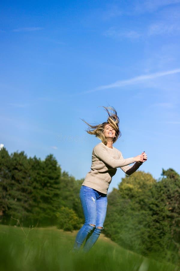 Fondo feliz del salto joven, del cielo y del árbol de la mujer foto de archivo