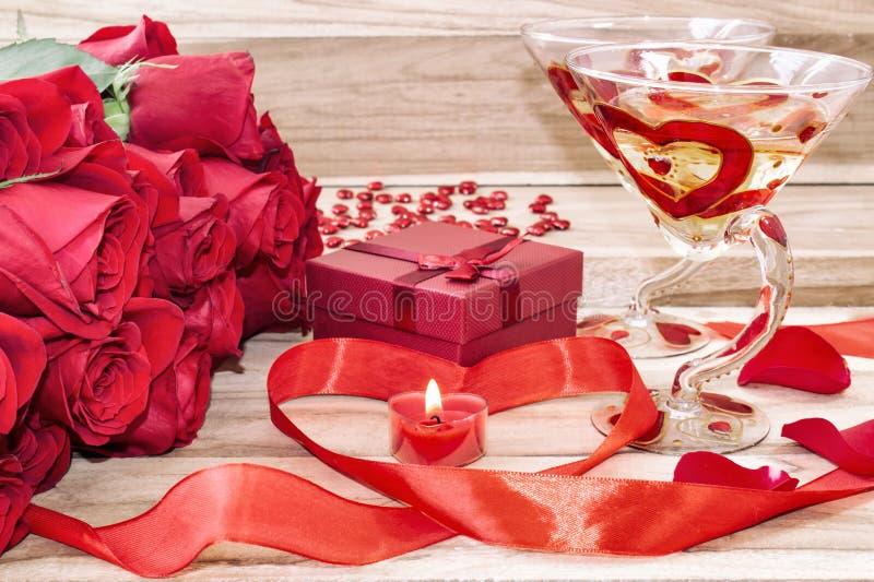Fondo festivo al día de tarjeta del día de San Valentín Un ramo de rosas rojas, de una caja de regalo, de una vela en forma de co fotos de archivo