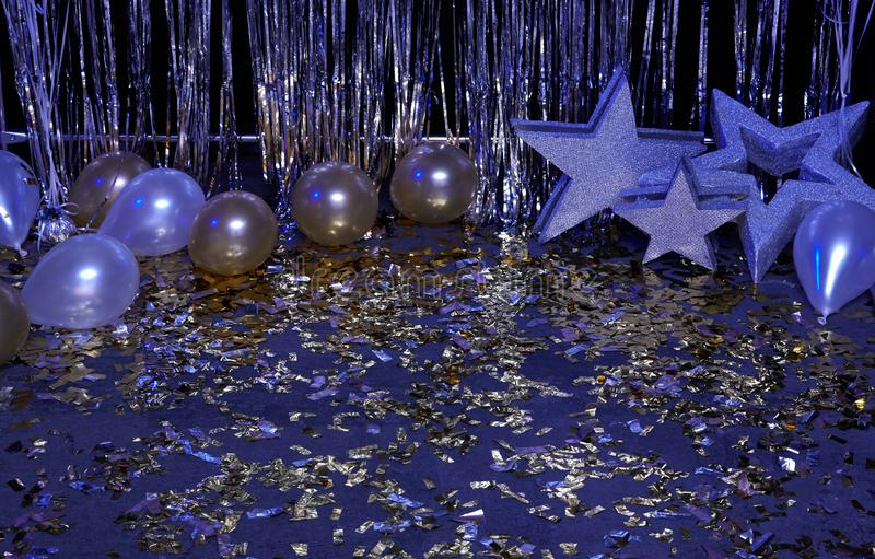 Fondo festivo azul de neón con los globos, las estrellas y el confeti iluminados por las linternas coloreadas fotografía de archivo