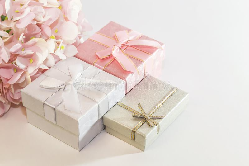 Fondo festivo con l'involucro di regalo con il rosa, le scatole d'argento e grige con l'arco ed i fiori dell'ortensia artificiale immagini stock libere da diritti