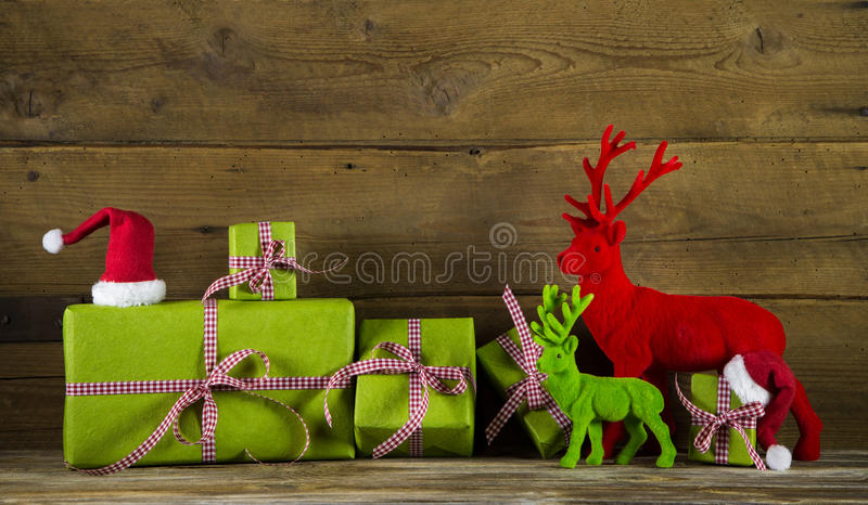 Fondo festivo de la Navidad con los presentes y reno en el rojo a foto de archivo