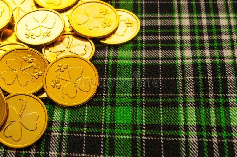 Fondo festivo del día del ` s de St Patrick Monedas de oro con el trébol en el paño a cuadros verde de la textura foto de archivo