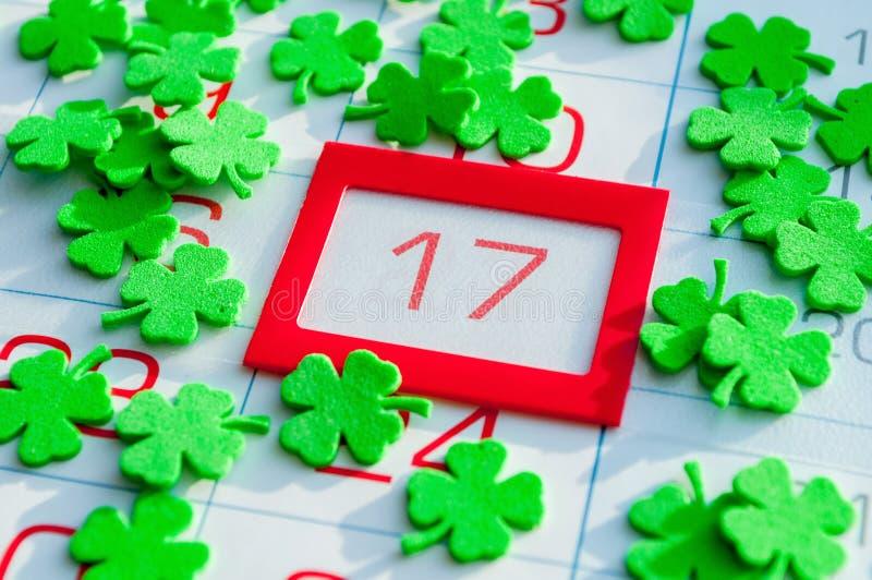 Fondo festivo del día del ` s de St Patrick Quatrefoils verdes que cubren el calendario con el 17 de marzo enmarcado rojo brillan fotos de archivo libres de regalías