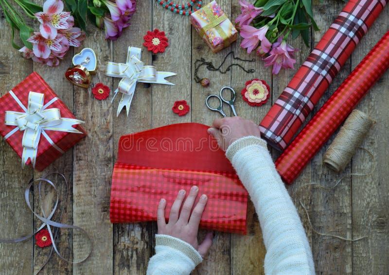 Fondo festivo La composición de la visión superior de las manos de la mujer envuelve el presente para el cumpleaños, día del ` s  foto de archivo libre de regalías