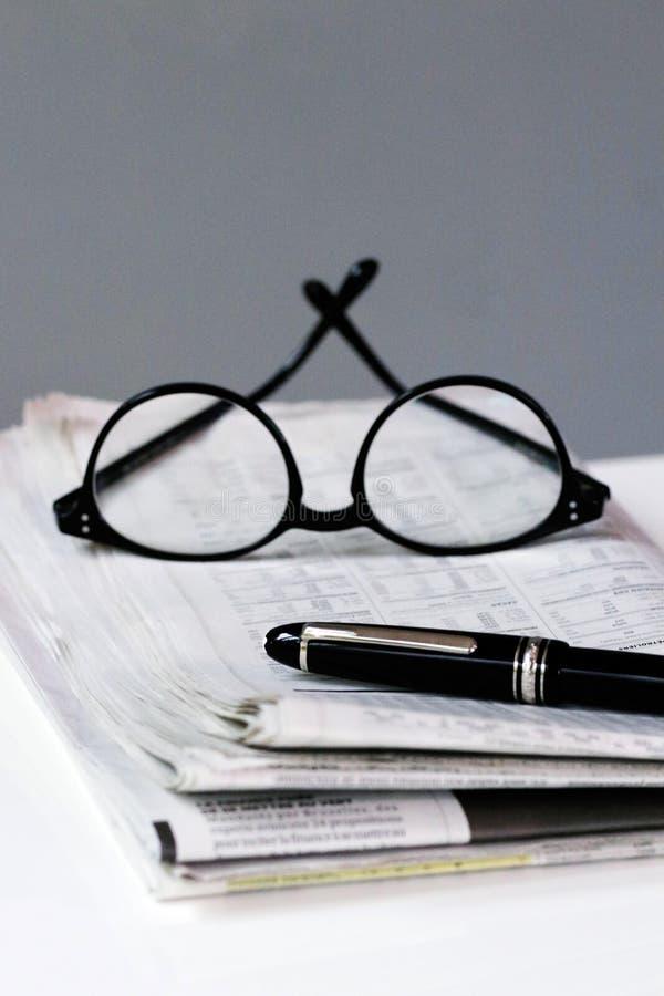 Fondo finanziario della rottura del giornale con l'uomo di affari di vetro e della penna fotografia stock libera da diritti