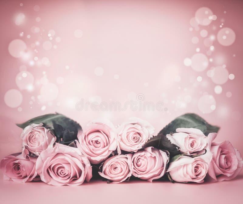 Fondo floral pálido rosado con el manojo de las rosas en la tabla con el bokeh Días de fiesta que saludan la disposición fotos de archivo