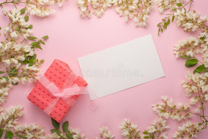 Fondo floreale della primavera con il regalo, la struttura e la carta da parati Fiori piani del fiore bianco su un fondo rosa-chi immagini stock