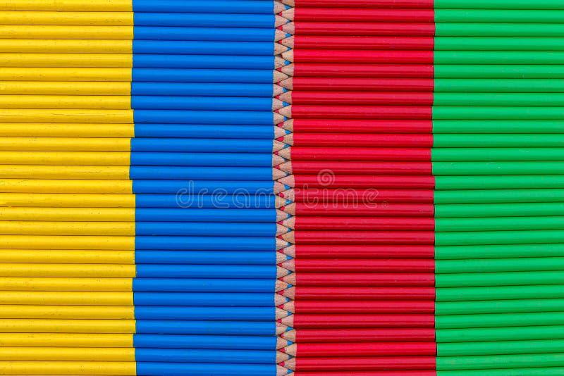 Fondo giallo, blu, rosso e verde composto di piccole matite fotografia stock libera da diritti