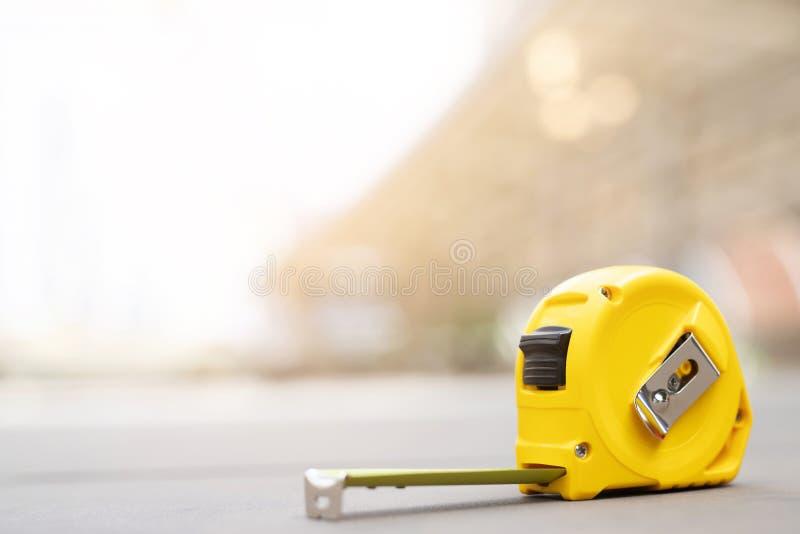 Fondo giallo di misura di nastro nel progetto al cantiere fotografia stock