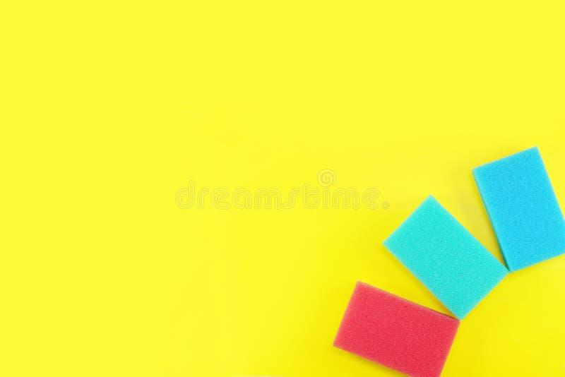 Fondo giallo sul tema di pulizia con le spugne variopinte immagini stock libere da diritti