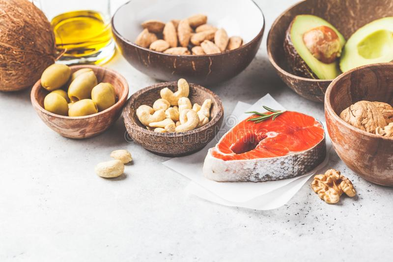 Fondo grasso sano dell'alimento Pesce, dadi, olio, olive, avocado su fondo bianco fotografie stock libere da diritti