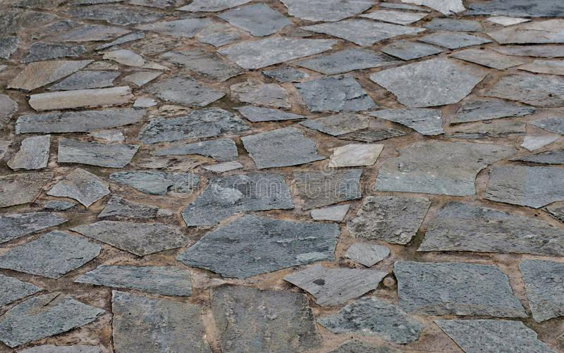 Fondo grigio di una strada fatta delle pietre delle dimensioni differenti vicino su fotografie stock