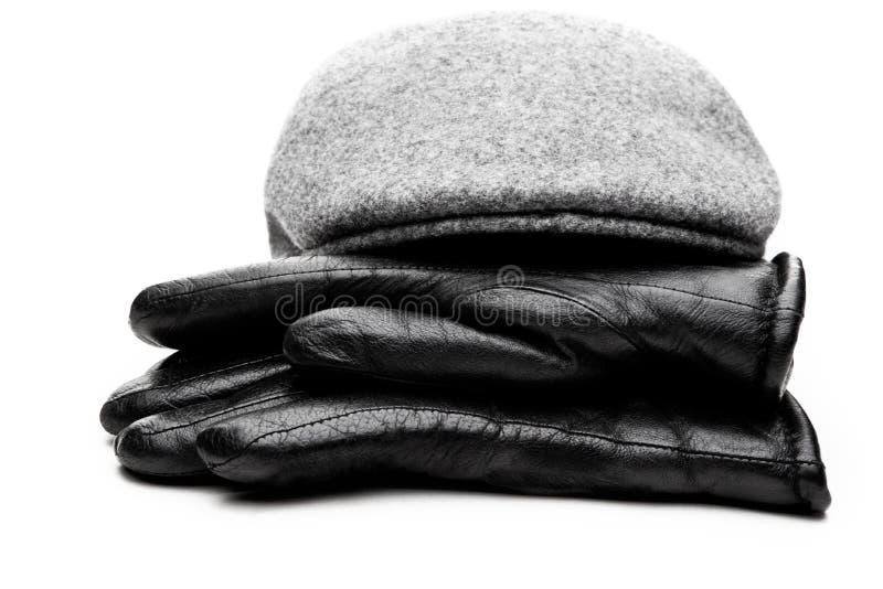 Fondo gris del blanco de los guantes de cuero del negro del casquillo del tweed fotografía de archivo libre de regalías