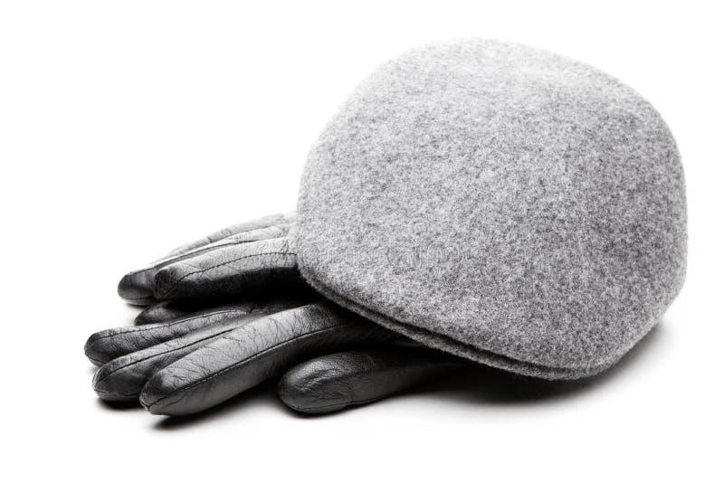 Fondo gris del blanco de los guantes de cuero del negro del casquillo del tweed imagen de archivo libre de regalías