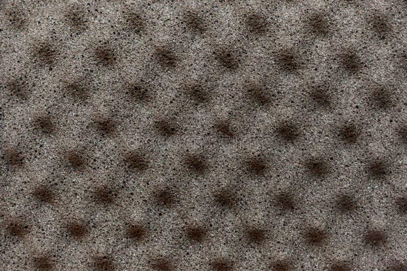 Fondo gris del material de la espuma con salientes piramidales en t foto de archivo