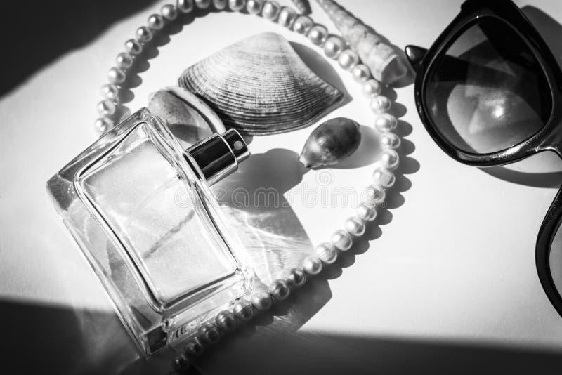 Fondo hermoso blanco con el perfume de las mujeres, las lentes de sol negros y las conchas marinas, fondo de las vacaciones, acce imagen de archivo libre de regalías