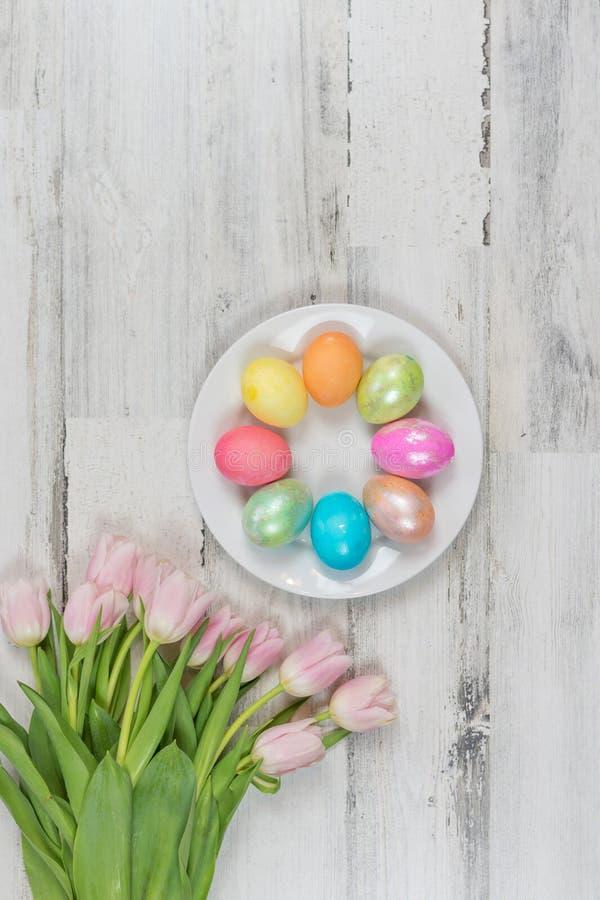 Fondo hermoso brillante de la primavera con los tulipanes frescos y los huevos de Pascua coloreados - formato vertical imagen de archivo